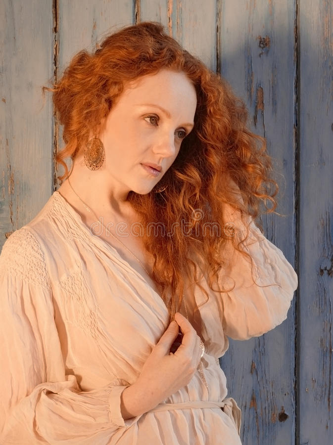 Sensueel vrouwelijk modelivory flame in peinzend stelt met lang draperend rood haar royalty-vrije stock afbeelding