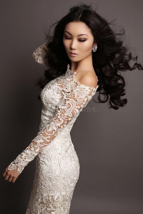 Sensuele Aziatische vrouw met lang donker haar in elegante kantkleding stock foto's