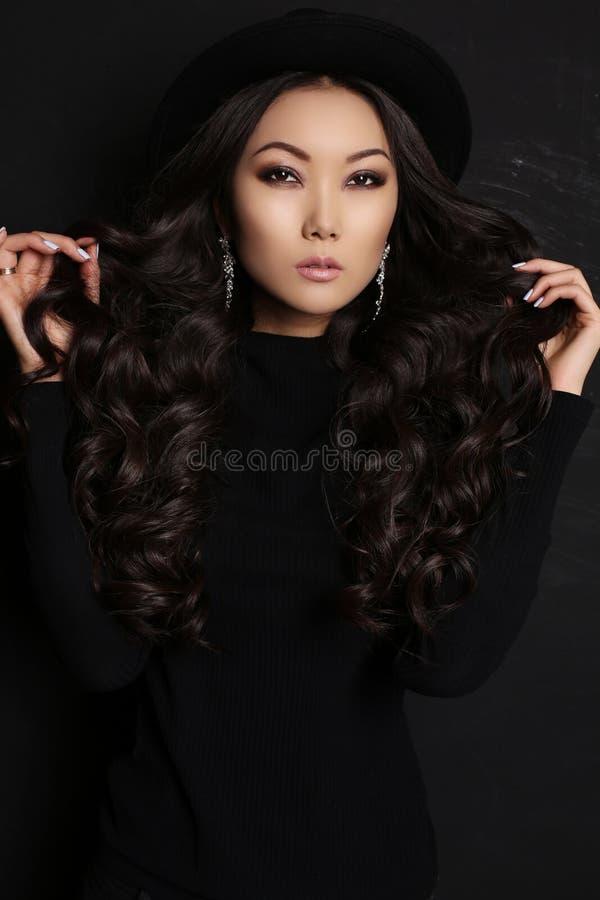 Sensuele Aziatische vrouw met lang donker haar in zwarte kleding stock afbeelding