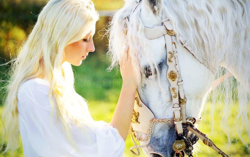 Sensuele blondenimf en majestueus paard royalty-vrije stock afbeelding