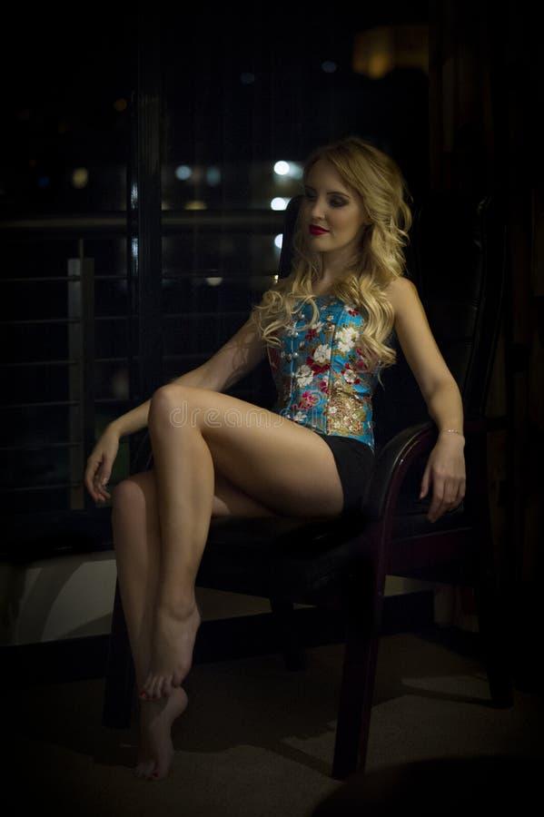 Sensuele blondevrouw in korset gezet voor een stadsvenster bij nacht royalty-vrije stock afbeeldingen