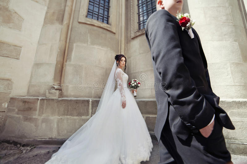Sensuele donkerbruine bruid in uitstekende witte kleding en knappe bruidegom royalty-vrije stock foto