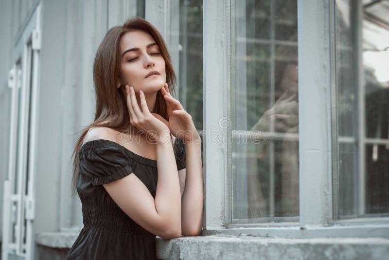 Sensuele donkerbruine vrouw die kleding met naakte schouders dragen, posin royalty-vrije stock fotografie