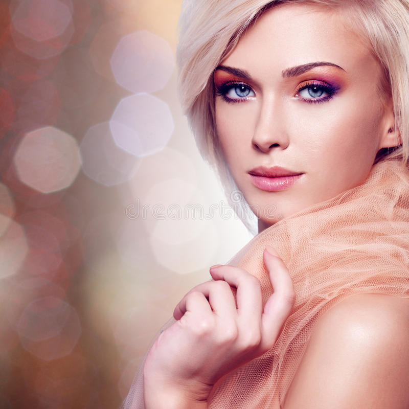 Sensuele jonge vrouw in de beige stof stock afbeelding