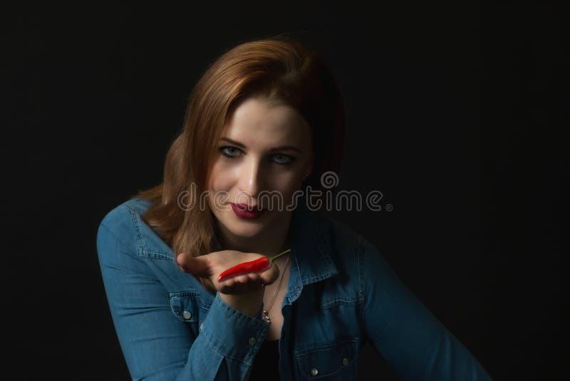 Sensuele jonge vrouw met rode Spaanse peperspeper royalty-vrije stock afbeelding