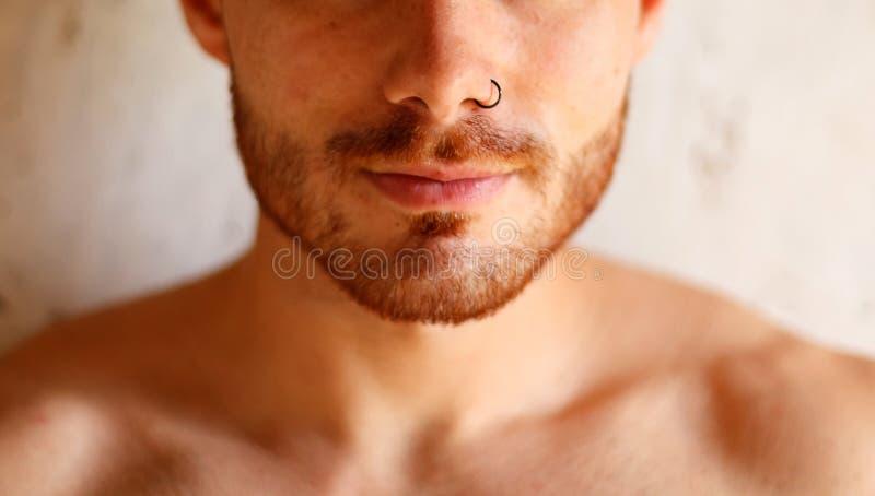 Sensuele kerel met het doordringen op zijn neus stock foto's