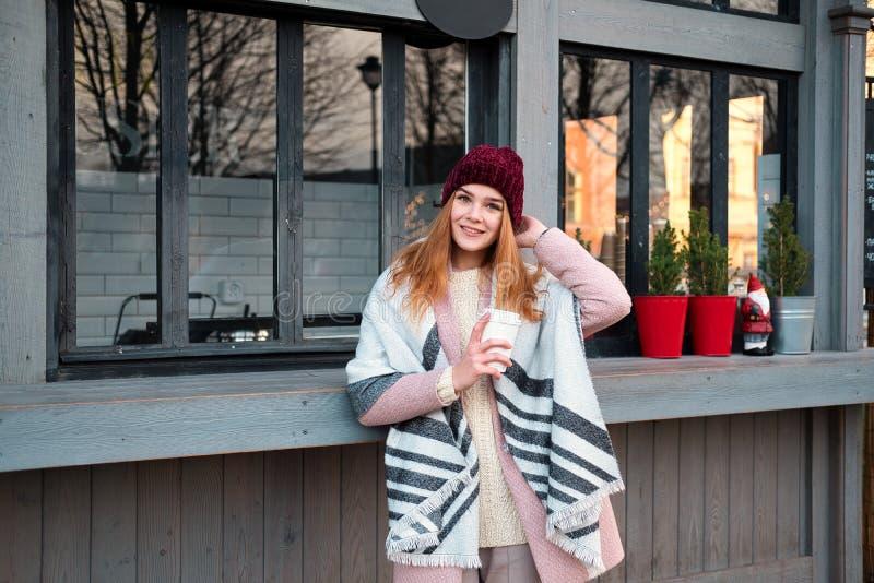 Sensuele modieuze jonge vrouw het drinken koffie op de straatkoffie in koud de winterweer stock foto's
