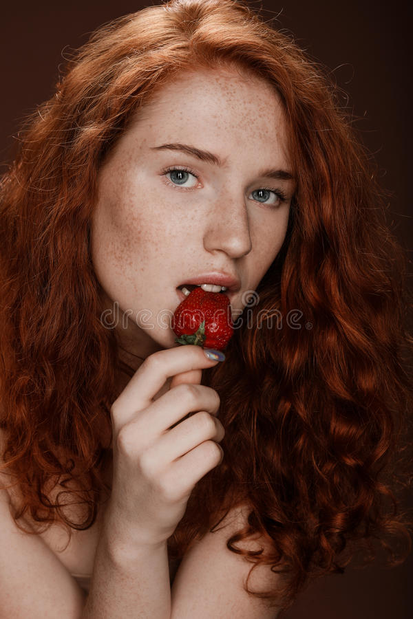 Sensuele roodharigevrouw die verse aardbei, op bruin eten stock afbeelding