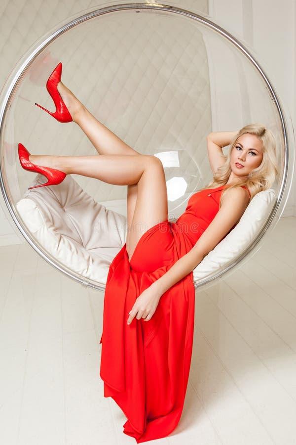 Sensuele schitterende modieuze blonde jonge vrouw in heldere avond rode kleding met en make-up en krullend kapsel die binnen ligg stock foto's