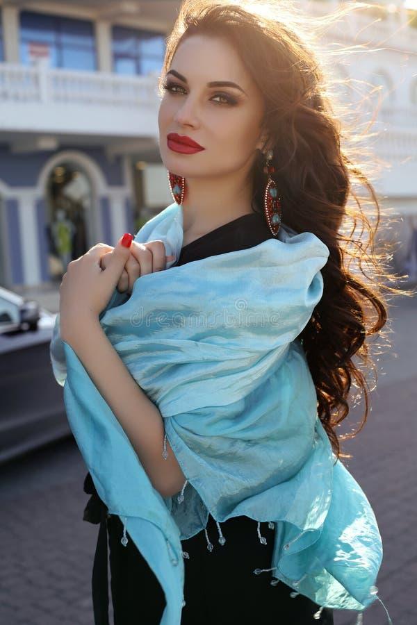 Sensuele vrouw die elegante zwarte kleding en zijdesjaal dragen stock afbeelding