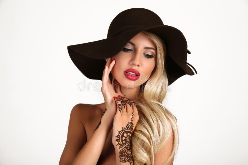 Sensuele vrouw in elegante zwarte hoed met hennatatoegering op handen royalty-vrije stock foto's
