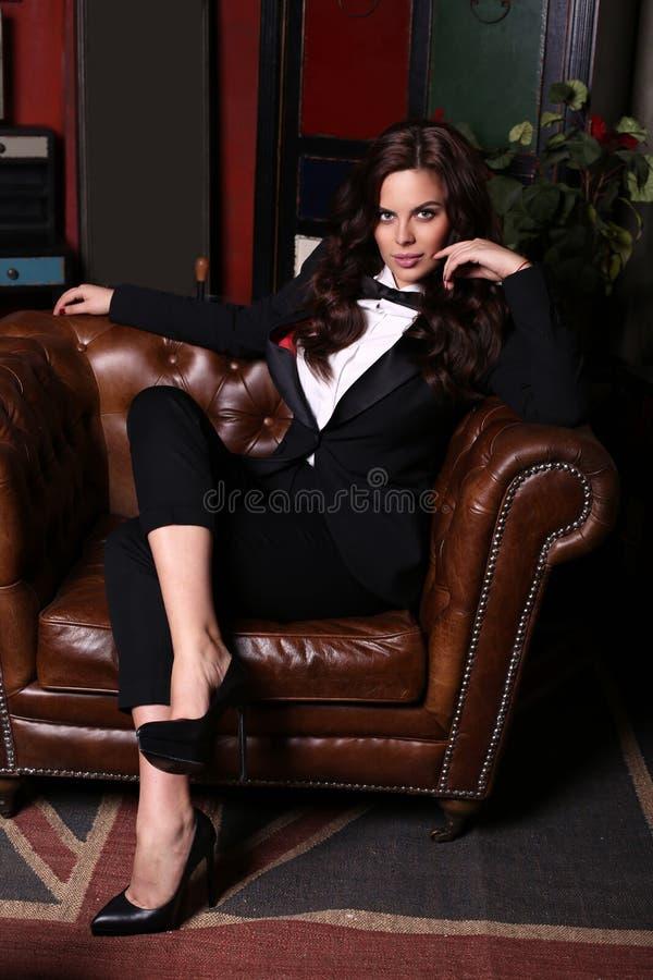 Sensuele vrouw met donker haar die elegant zwart kostuum dragen royalty-vrije stock afbeeldingen