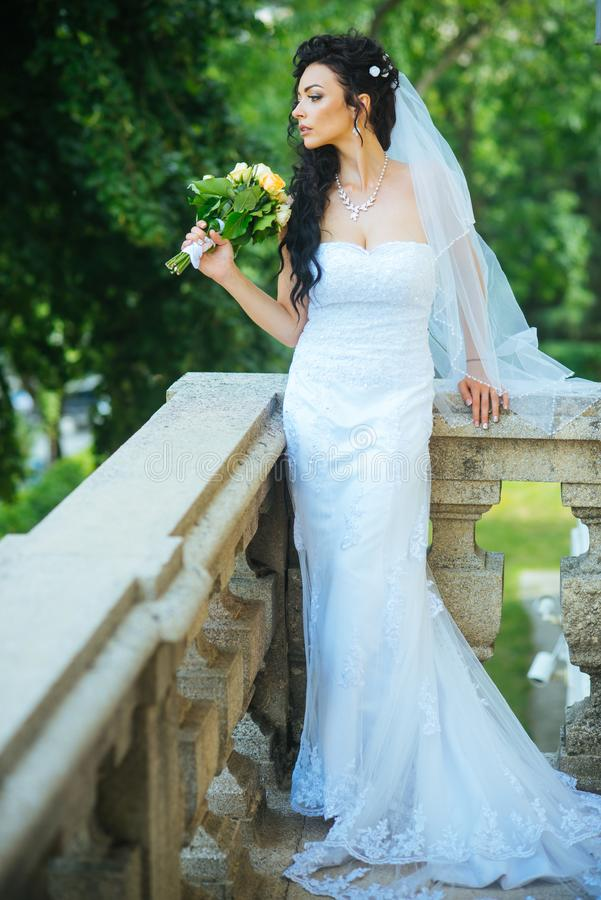 Sensuele vrouw met huwelijksboeket Vrouw met bloemen op balkon Schoonheidsmeisje met bruids make-up en kapsel Bruid stock fotografie