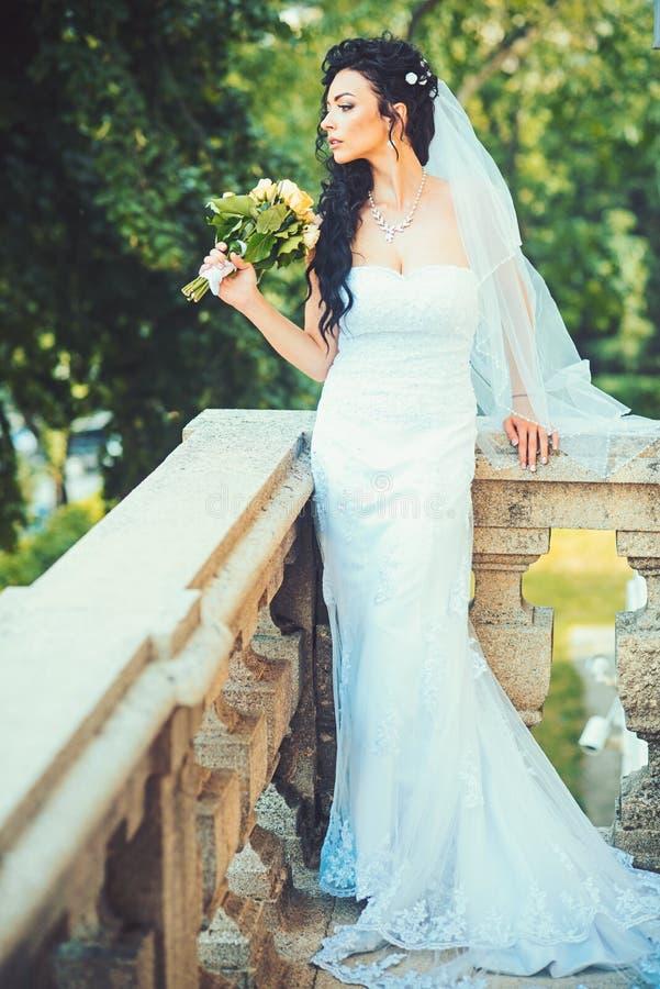 Sensuele vrouw met huwelijksboeket Vrouw met bloemen op balkon Schoonheidsmeisje met bruids make-up en kapsel Bruid royalty-vrije stock fotografie