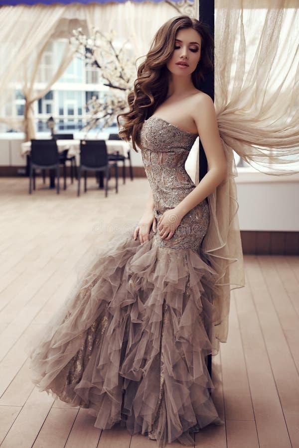 Sensuele vrouw met lang donker haar in luxueuze lovertjekleding stock foto's