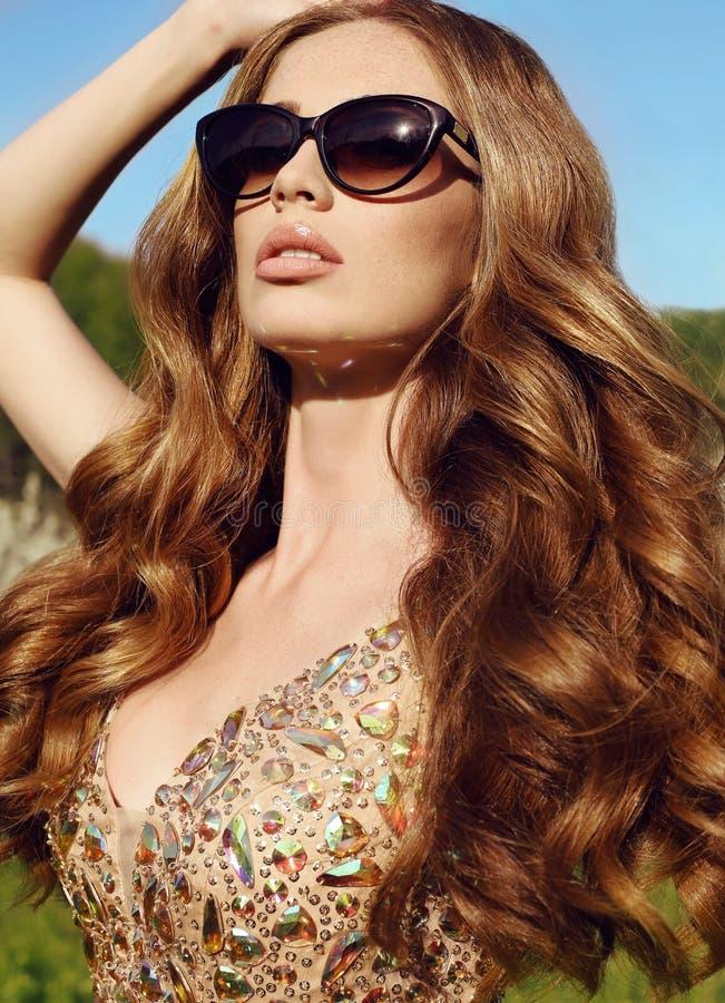 Sensuele vrouw met lang rood haar in luxueuze lovertjekleding met zonnebril royalty-vrije stock foto