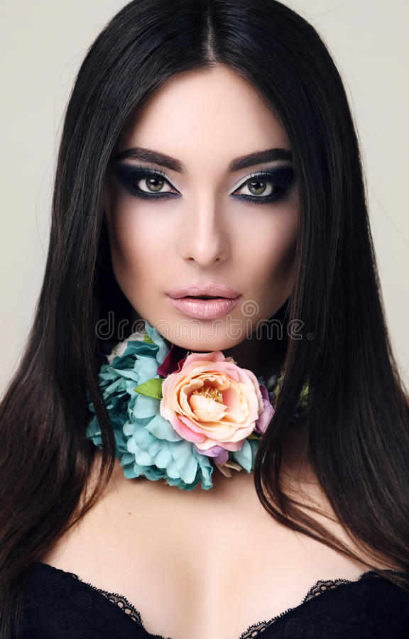 Sensuele vrouw met recht zwart haar met heldere make-up en van de bloem halsband stock fotografie