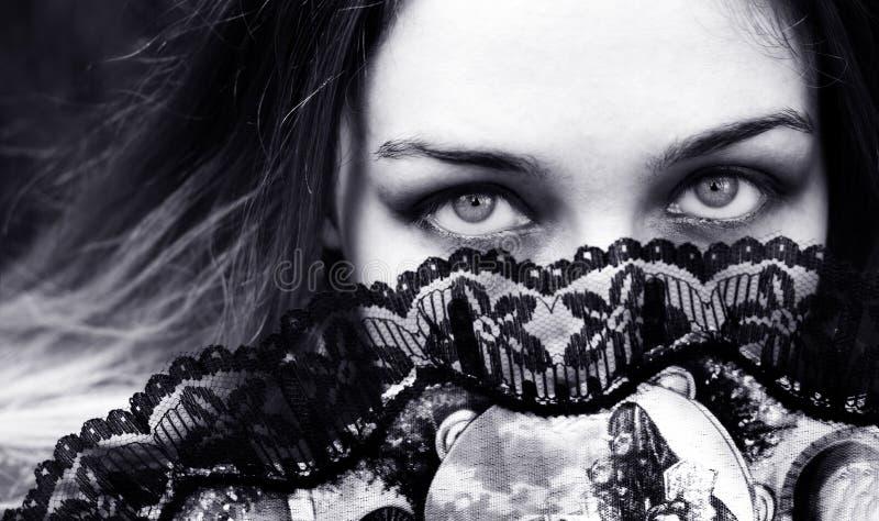 Sensuele vrouw met verleidelijke ogen achter ventilator royalty-vrije stock foto's