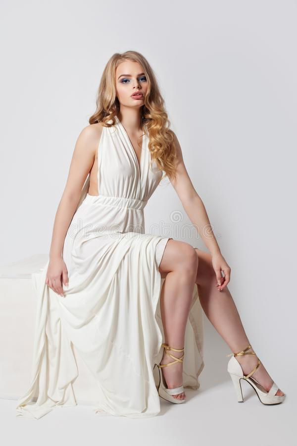 Sensuele vrouw in witte avondtoga Schoonheidsmodel met perfecte benen in hoge hielen royalty-vrije stock foto's