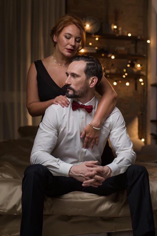 Sensuele vrouwen uitnodigende man aan beddegoed stock foto's