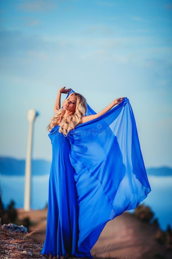 Sensuele vrouwentribune op de steen van piekberg blonde vrouw met lange haargang op de rand en het kijken van de klip neer royalty-vrije stock fotografie