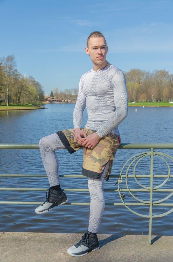 Sentándose en una verja por el río, hombre atractivo en el deporte blanco imágenes de archivo libres de regalías