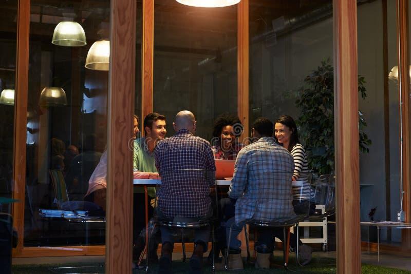 Sent - nattmöte runt om tabellen i designkontor arkivbild
