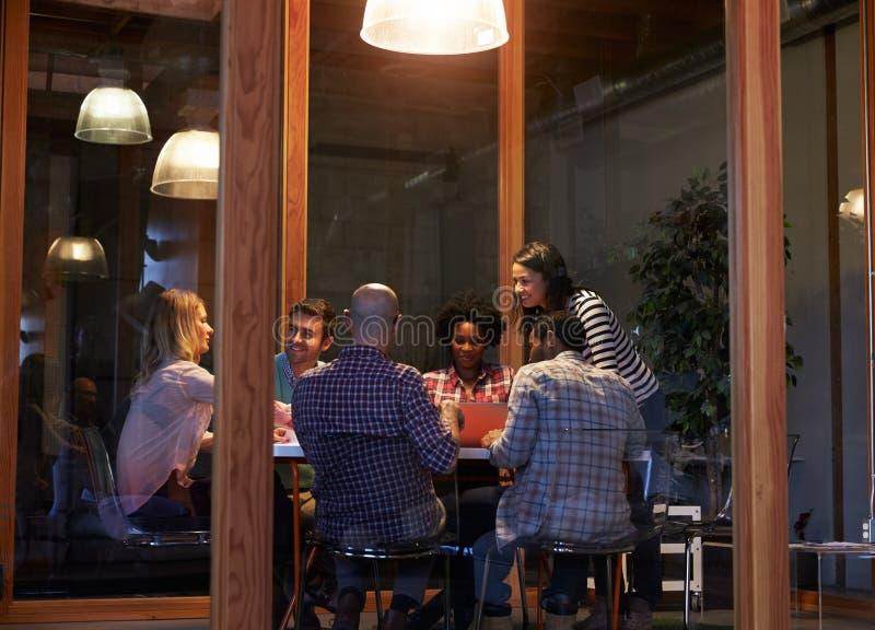 Sent - nattmöte runt om tabellen i designkontor royaltyfri bild