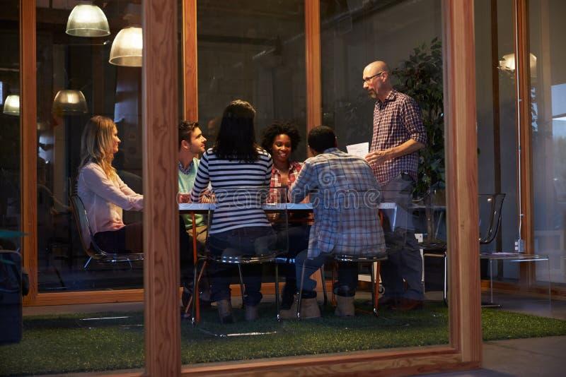 Sent - nattmöte runt om tabellen i designkontor royaltyfri fotografi