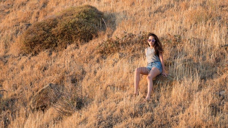 Sentada adolescente en cepillo seco en el lado de una montaña con el pur del sol fotos de archivo