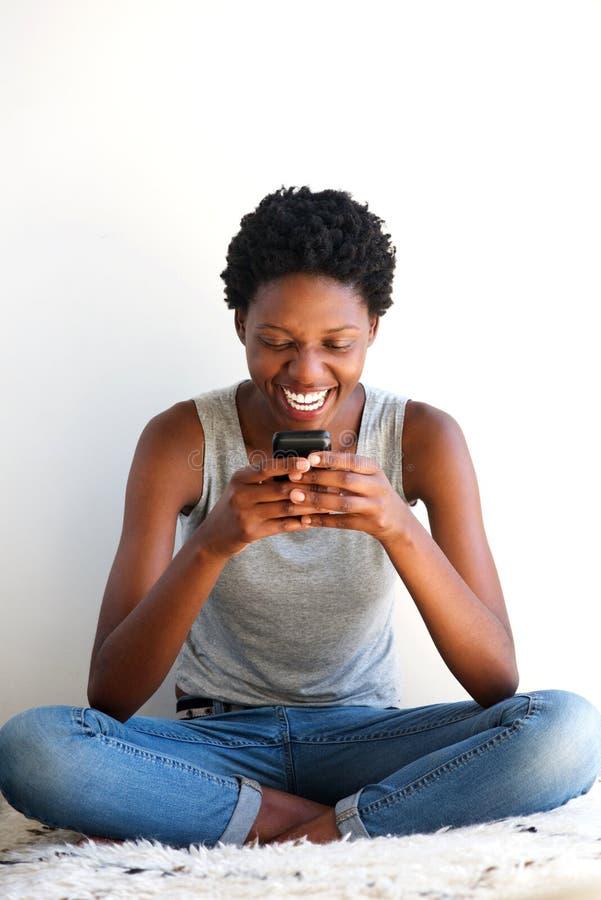 Sentada africana joven alegre de la mujer y usar el teléfono móvil foto de archivo