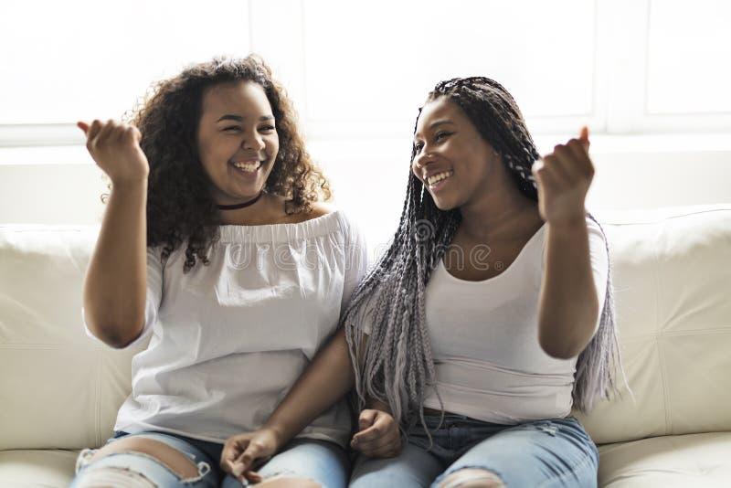Sentada afroamericana de los amigos cariñosos en el sofá imágenes de archivo libres de regalías