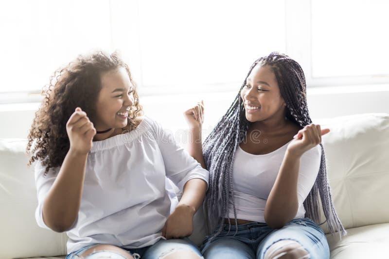 Sentada afroamericana de los amigos cariñosos en el sofá foto de archivo libre de regalías