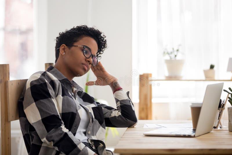 Sentada agujereada sensación afroamericana de la muchacha en el lugar de trabajo imagen de archivo