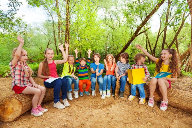 Sentada al aire libre linda de los libros de lectura de los niños en el registro fotos de archivo libres de regalías