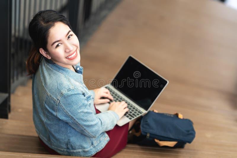 Sentada asiática de la mujer del retrato, usando el ordenador portátil, sonriendo y mirando la cámara imágenes de archivo libres de regalías