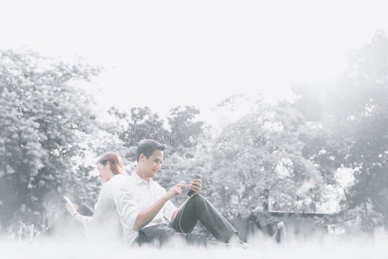Sentada asiática joven de los pares del estudiante universitario y relajación junto en el parque, escuchando la música en smartph imagen de archivo