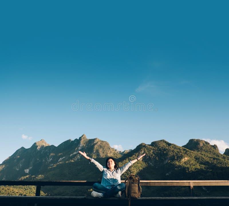 Sentada asiática y brazos del viajero de la mujer para arriba en el aire en la terraza del punto de visión en la opinión del pais imagen de archivo