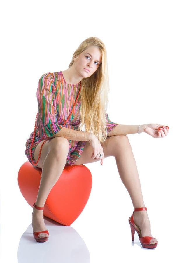 Sentada blondy hermosa en corazón y la presentación rojos fotos de archivo