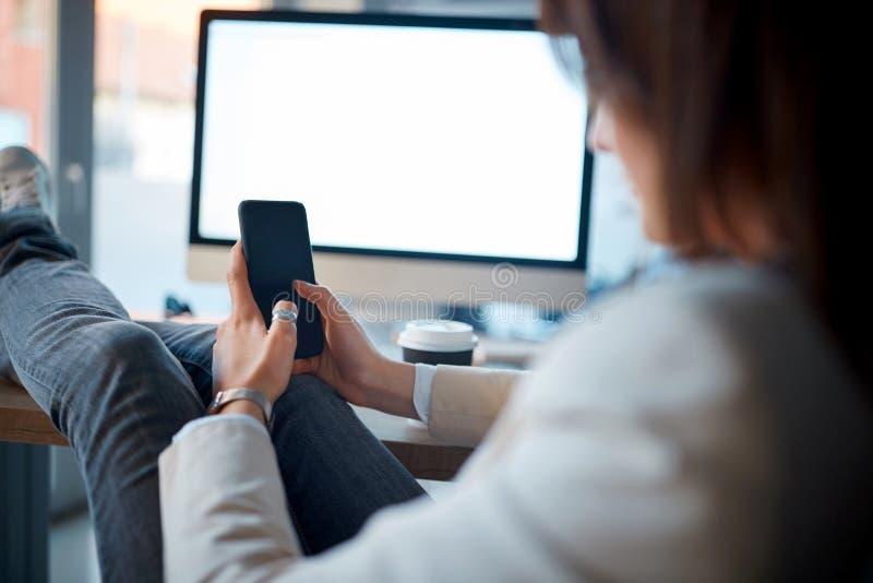 Sentada creativa de la mujer del diseñador y usar el teléfono móvil en el workpl imagen de archivo libre de regalías