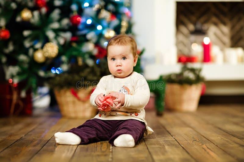 Sentada de 1 año del pequeño bebé lindo rechoncho en el piso adentro imagenes de archivo
