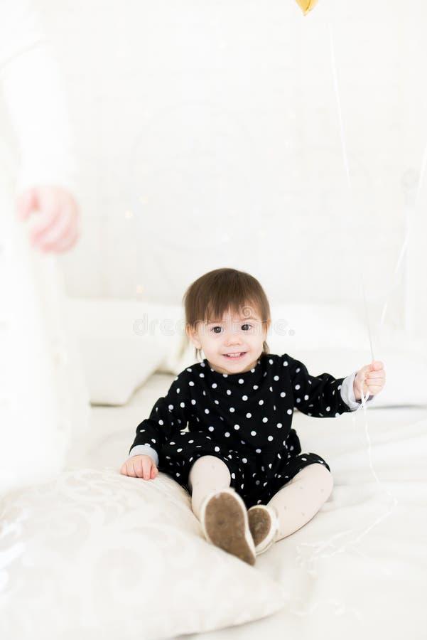 Sentada de 2 años del bebé lindo en una cama con un globo Fiesta de cumplea?os celebraci?n fotos de archivo