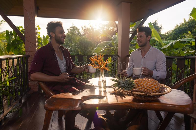 Sentada de dos mangos en la taza del control de la terraza del verano que desayuna que habla, individuos en café de consumición d imagenes de archivo