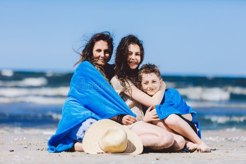 Sentada de la madre, de la hija y del hijo envueltos en una manta imagen de archivo