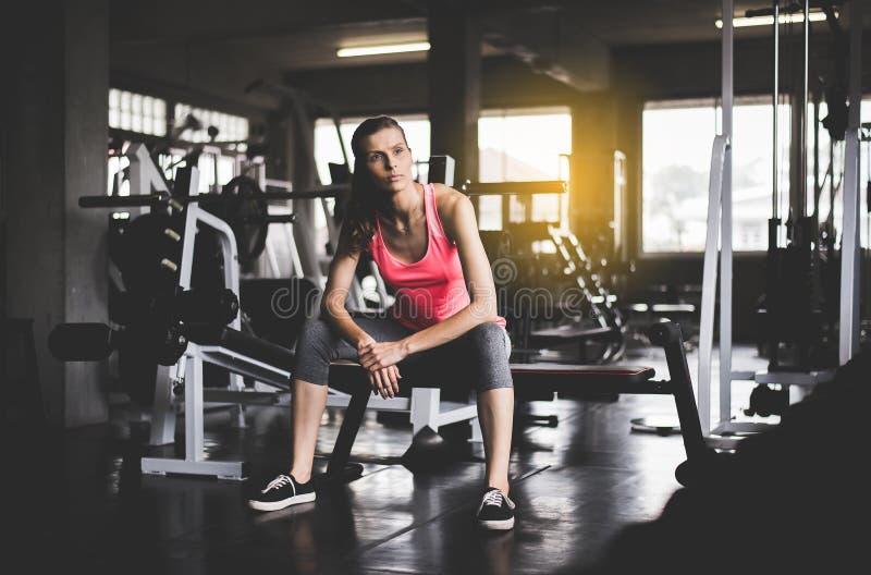 Sentada de la mujer del ajuste y relajarse después de la sesión de formación en gimnasio, del concepto sano y de la forma de vida foto de archivo