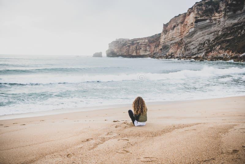 Sentada de la mujer en la playa de Océano Atlántico en Portugal imágenes de archivo libres de regalías