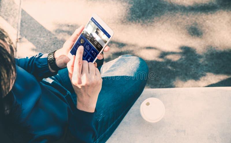 Sentada de la mujer y control casero elegante app del uso en el teléfono móvil y foto de archivo libre de regalías