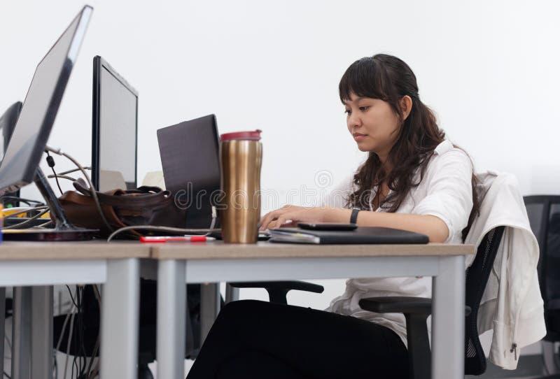 Sentada de trabajo del ordenador de la empresaria asiática imagen de archivo