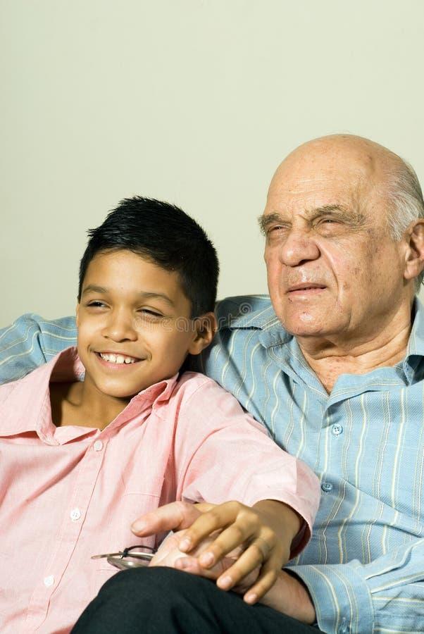 Sentada del abuelo y del nieto - vertical imagen de archivo