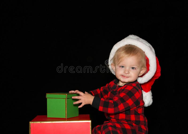 Sentada del bebé con los regalos de Navidad que llevan a Santa Hat que mira el espectador foto de archivo